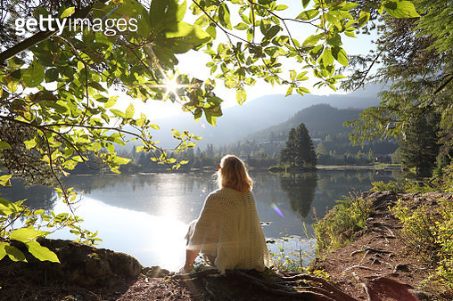 He looks off to distant mountain, forest and lake scene - gettyimageskorea