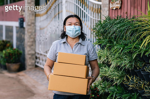 Asian woman positive smiling wear N95 cloth face mask for close mouth and sick on nose with cold cough and Covid-19 while standing holding a package. - gettyimageskorea