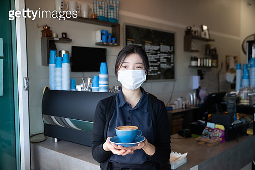 Confident coffee shop owner holding coffee cup and wearing facemask after reopening - gettyimageskorea