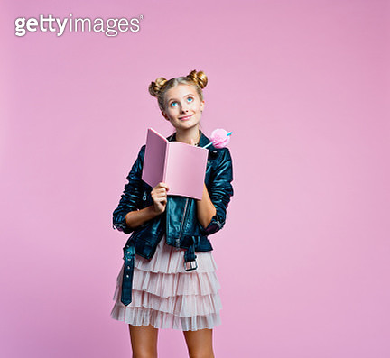 Surprised female teenager wearing black leather jacket and pink tulle skirt holding pink notebook and pen in hands. Cute girl looking up. Studio shot on pink background. - gettyimageskorea