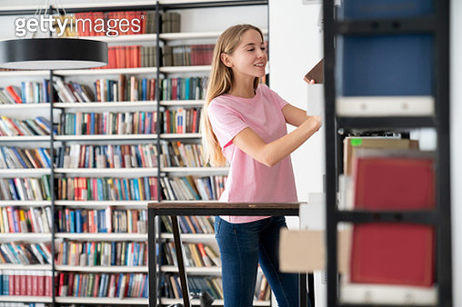Happy librarian organizing books at the library - gettyimageskorea