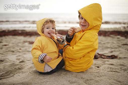 A boy and his little sister on the beach, they wear oilskins - gettyimageskorea