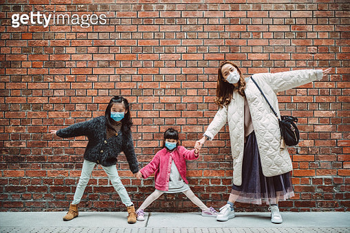 Mom & daughters in medical face masks taking picture in front of brick wall - gettyimageskorea