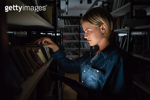 Student searching for a book at nighttime at the library - gettyimageskorea