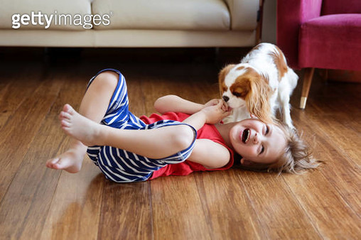 Little boy lying on the floor in the living room laughing because his dog licking his hand - gettyimageskorea