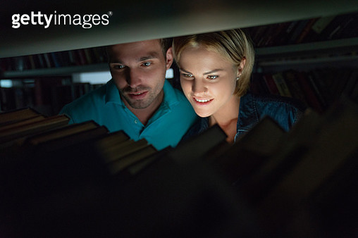 Couple of students searching for a book at nighttime at the library - gettyimageskorea