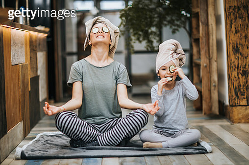 Mother and little girl taking care of their bodies in the morning while doing Yoga meditation exercises at home. Girl is cheating while eating cucumbers from her eyes and looking at camera. - gettyimageskorea
