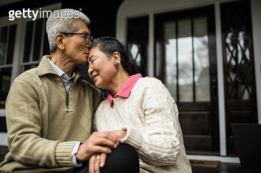 Senior couple embracing in front of home - gettyimageskorea