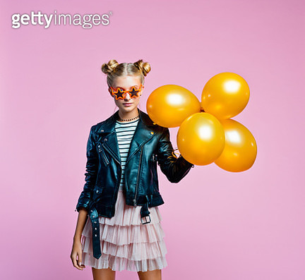 Surprised female teenager wearing black leather jacket, pink tulle skirt and star shaped sunglasses holding bunch of gold balloons. Smiling girl going to the party. Studio shot on pink background. - gettyimageskorea