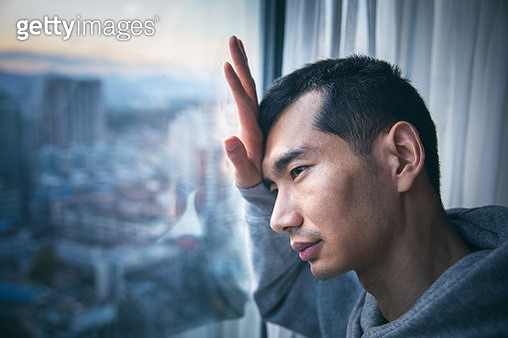 Sadness man against the window - gettyimageskorea