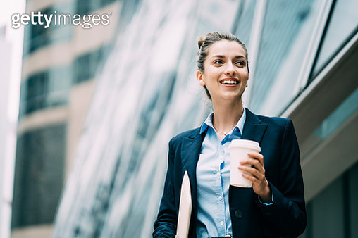 Young businesswoman holding documents and coffee cup, walking on street. - gettyimageskorea