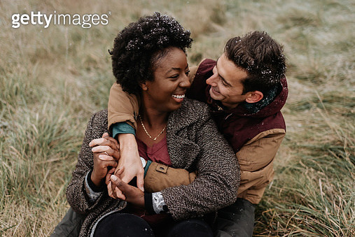 A black woman and white man hugging each other and smiling, sitting in a field of grass. - gettyimageskorea