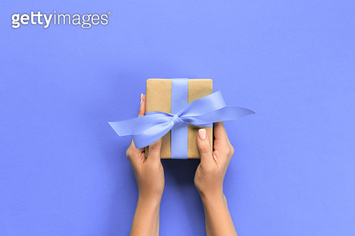 Cropped Hands Of Woman Holding Wrapped Gift Box Over Colored Background - gettyimageskorea