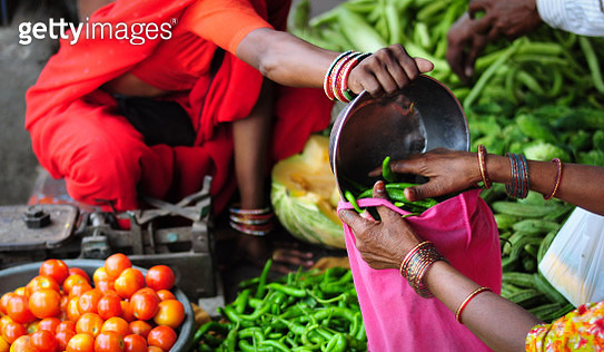 At an impromptu market place in India, a lady is purchasing green chili. The vendor helps transfer the chili from a measuring bowl into a reusable textile bag. - gettyimageskorea