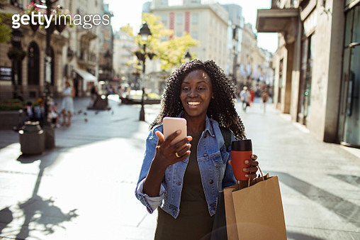 Close up of a young woman using a phone while out shopping - gettyimageskorea