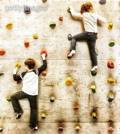 Full Length Of Siblings Climbing On Wall - gettyimageskorea