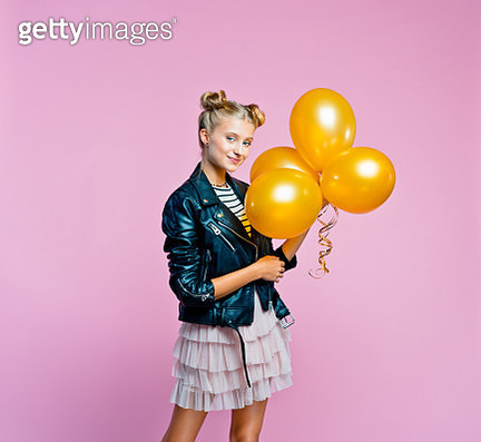 Cute female teenager wearing black leather jacket and pink tulle skirt holding bunch of gold balloons. Smiling girl going to the party. Studio shot on pink background. - gettyimageskorea