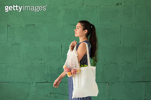 Young woman with shopping cotton Eco bag with fruits and vegetables in her hands on green wall background. Lifestyle, zero waste concept - gettyimageskorea