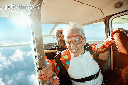 Close up of a senior woman and her instructor doing tandem skydiving - gettyimageskorea