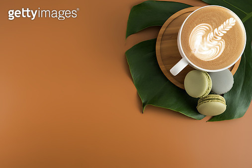 Close-Up Of Coffee Cup And Macaroons On Leaf Over Brown Background - gettyimageskorea