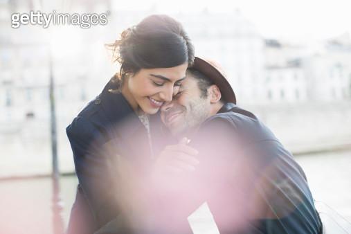 Couple hugging along Seine River, Paris, France - gettyimageskorea