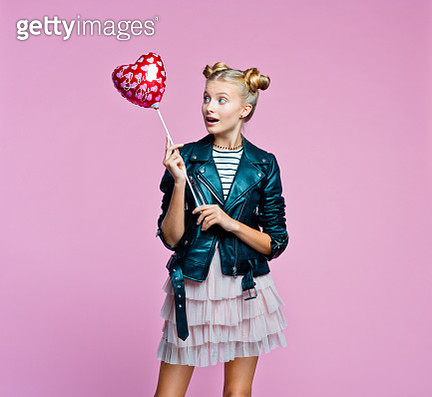 Surprised female teenager wearing black leather jacket and pink tulle skirt holding red heart shaped balloon in hand. Studio shot on pink background. - gettyimageskorea