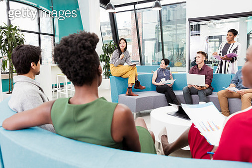 Businesswoman leading informal meeting in modern open plan office - gettyimageskorea