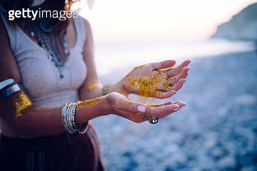 Boho woman at beach with golden glitter on her hands - gettyimageskorea