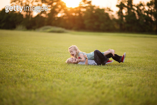 Young siblings laying in grass laughing - gettyimageskorea
