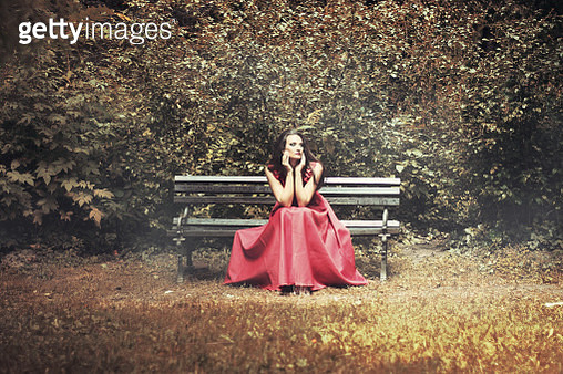 Portrait of woman in red evening dress sitting on beach - gettyimageskorea