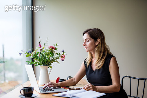Mature woman with laptop indoors at the table, working. - gettyimageskorea