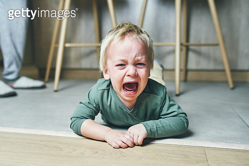 A little boy with blond hair, two years old, is lying on the floor and crying hysterically after kindergarten at home. Parenting. - gettyimageskorea