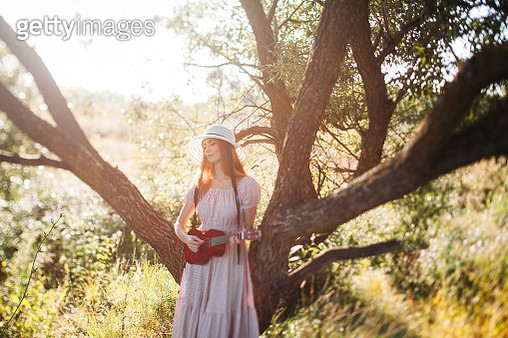 a beautiful girl in a pink dress and a hat with a brim plays a ukulele under the spreading branches of a flowering tree. romantic image, warm sunlight at sunset - gettyimageskorea