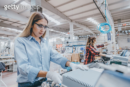 Professional young industrial factory woman employee working with machine parts putting, checking and testing industrial equipments cables in large Electric electronics wire and cable manufacturing plant factory warehouse - gettyimageskorea