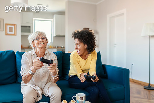 Cheerful Elderly Mother and Her Adopted African Daughter Playing Video Console Game at Home in the Livingroom. Senior Mother With Mixed Race Daughter Playing Video Game Using Joystick, Having Fun Together - gettyimageskorea