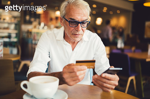 Senior man in cafe shopping online with credit card - gettyimageskorea
