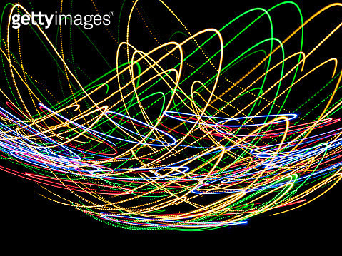 Close-up abstract pattern of intertwined colorful red, yellow and blue lights on a black background. - gettyimageskorea