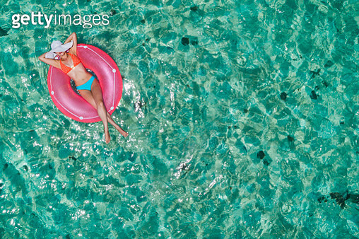 Aerial view of a young women relaxing on inflatable ring in a tropical turquoise pristine beach. Los Juanes, Morrocoy, Venezuela - gettyimageskorea