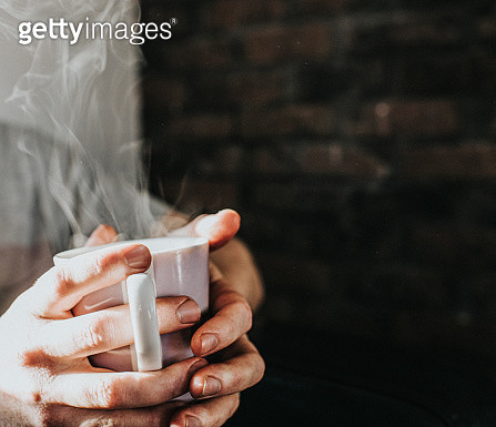 Hands gripping a hot, steaming mug of coffee - gettyimageskorea