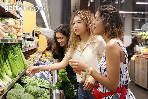 Three female LatinX millennials shop for vegetables at a grocery store, wearing summer clothes. - gettyimageskorea