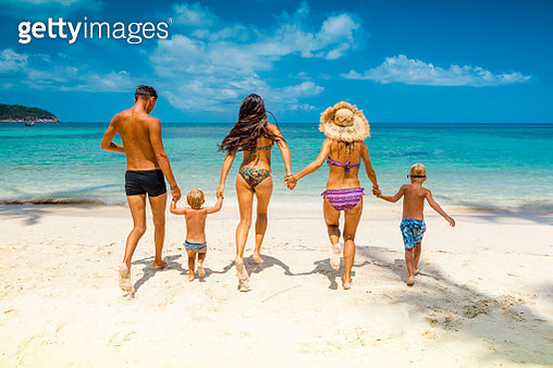 Friends playing in waves on beach - gettyimageskorea