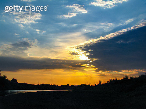 Scenic View Of Dramatic Sky Over Silhouette Landscape During Sunset - gettyimageskorea