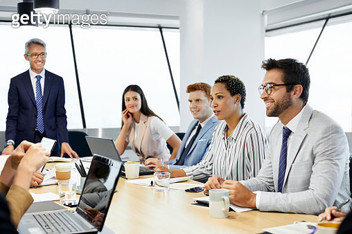 Male and female professionals discussing at conference table. Business colleagues are planning in meeting. They are at board room in office. - gettyimageskorea