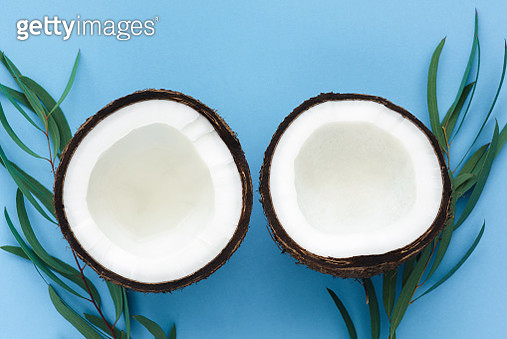 Two coconut halves on blue background - gettyimageskorea