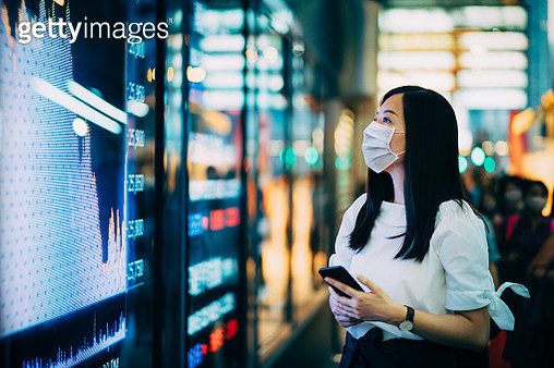 Economic and financial impact during the Covid-19 health crisis deepens. Businesswoman with protective face mask checking financial trading data on smartphone by the stock exchange market display screen board in downtown financial district showing stock m - gettyimageskorea