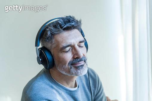 Mature man with closed eyes wearing headphones - gettyimageskorea