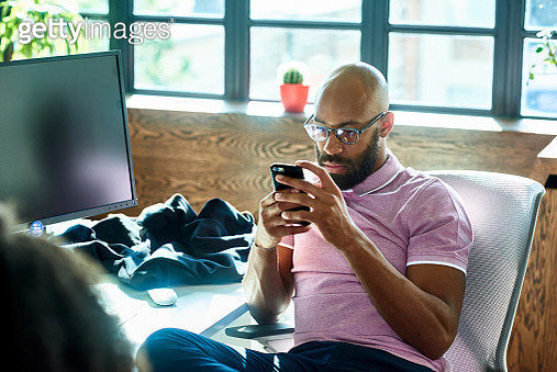 Mid adult man with beard and glasses texting in office - gettyimageskorea