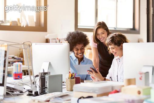 Happy businesswomen using digital tablet in office - gettyimageskorea