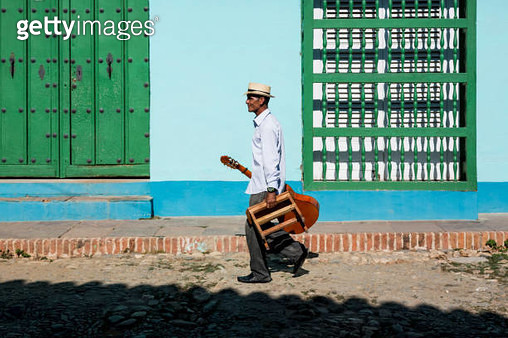 Cuba, Trinidad, walking man with guitar and stool on the street - gettyimageskorea
