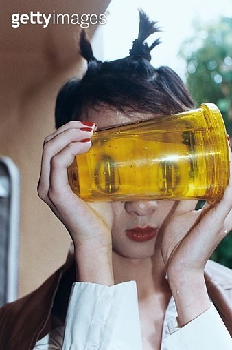 Young adult holding a cup of water to their face - gettyimageskorea